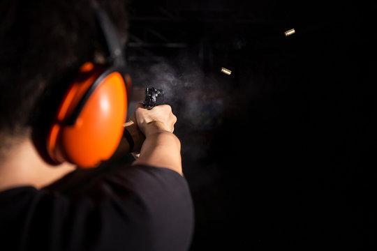 man shooting pistol gun, fire bullet, and wear orange ear cover in shooting range