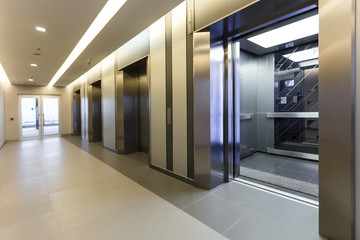 Modern steel elevator cabins in a business lobby or Hotel, Store, interior, office,perspective wide angle. Three elevators in hotel lobby..