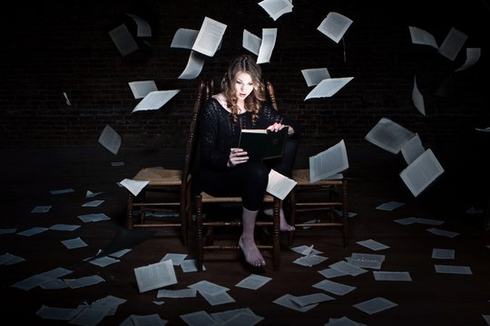 A young woman sits reading a magical book in a dark room with book pages flying all around her.  Great concept for the magic of reading.