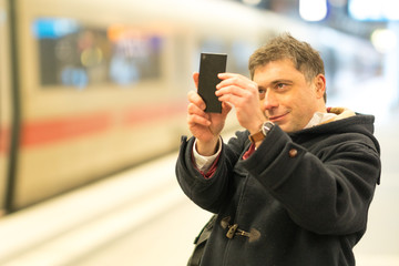 Passenger taking photos with his smartphone from railway station platform