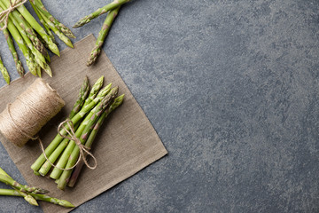 Bunch of fresh green asparagus on dark wooden background, top view