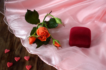 An orange rose and a box for jewellery on a pink cloth