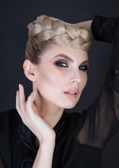Crown made from hair. Strong dark makeup. Elegant and chic look.