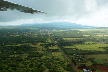 Landscape of Molokai, one of the Hawaiian Islands, aerial view showing the wing of a small airplane