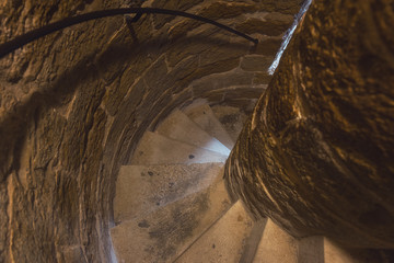 Narrow tight spiral stairs in ancient stone tower