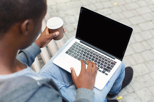 Male hands with laptop and coffee closeup,over shoulder shot outdoors