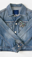Jeans denim woman jacket with vintage brooch on white background. Fashion outfit