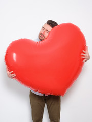 Enamored man hugging a big heart shaped red balloon