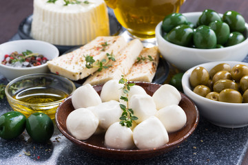 cheeses - mozzarella, feta cheese and pickles on table