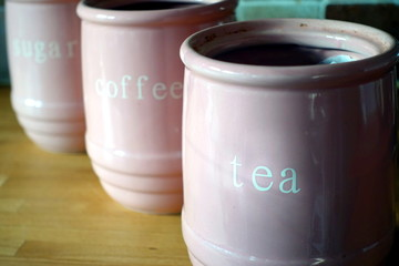 Three pink jugs on a wooden kitchen work surface, with the words Tea, Coffee and Sugar