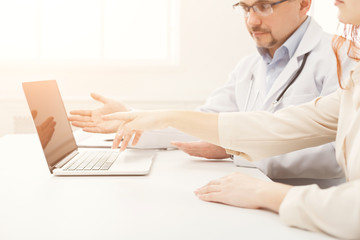 Closeup of a doctor and patient sitting at the desk