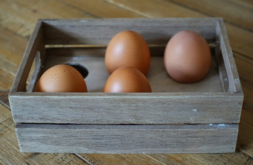 Four brown eggs in a wooden box with space for six eggs, in window light