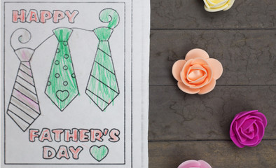Fathers day composition - child's drawing and multi-colored fake roses. Studio shot on wooden background.
