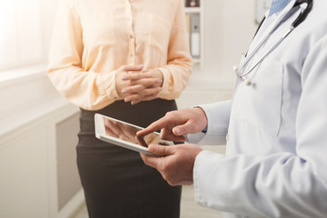 Closeup of a doctor pointing into tablet and patient