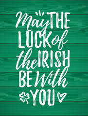 May The Luck Of The Irish Be With You handdrawn dry brush style lettering on green wooden background, 17 March St. Patrick's Day celebration. Suitable for greeting card design, poster, etc.
