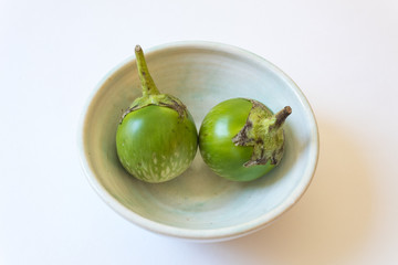 Two round green Thai eggplant Solanum melongena in a shallow bowl, isolated on white, horizontal aspect