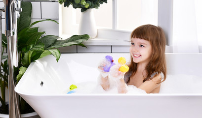 Happy little baby girl kid sitting in bath tub  in the bathroom