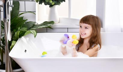 Happy little baby girl kid sitting in bath tub  in the bathroom