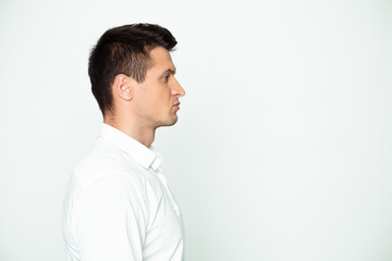 Side view portrait of a modern confident young businessman on a white background.