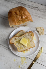 homemade sliced white bread with butter on rustic table