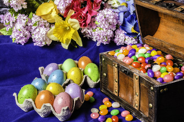 wood chest full of Easter jelly beans colored eggs and spring flowers on blue background