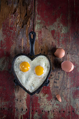 Valentines breakfast in heart shaped cast iron pan of two fried eggs
