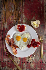 Plate of Valentines breakfast of two heart shaped fried eggs with heart shaped bisqutes with strawberry jam