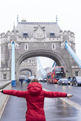 Girl in red coat embracing the Tower Bridge