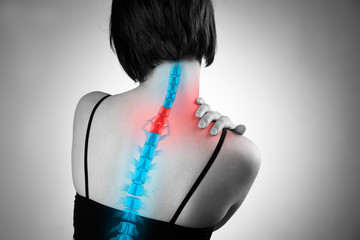 Pain in the spine, woman with backache, injury in the human back and neck