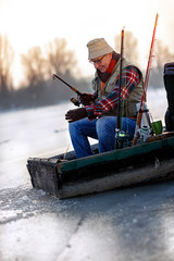 fisherman with fishing rod sit on frozen river in the winter