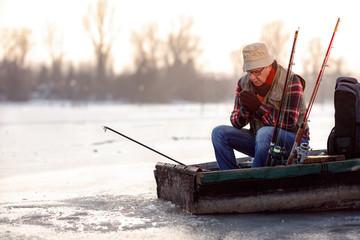 Winter season- man fishing on the frozen river