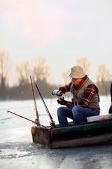 Ice fishing. elderly man sitting on frozen lake and drink tea