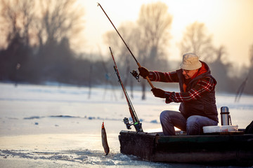 ice fishing on frozen lake- smiling fisherman catch fish pike