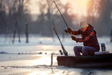 Spoed Fotobehang Vissen fisherman fishing on ice at the sunrise