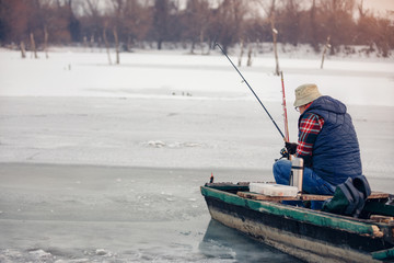 Winter season man fishing on frozen lake