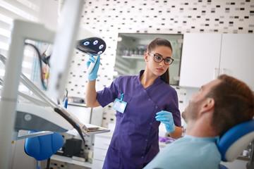 Dentist adjust reflector lamp before repairing teeth