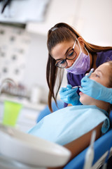 Dentist repairing tooth to female patient in dental chair