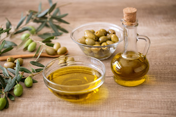 Extra virgin healthy Olive oil with olive on wooden background.