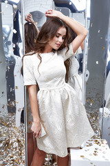 Brunette hair woman wear fashion white dress party style pretty beautiful face model pose catalog fashion clothes celebrate mirror sequins background studio sexy elegant lady date fun accessory bag.