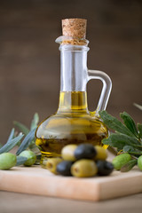 Olive oil in bottle on the wooden table.