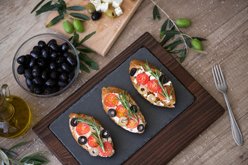 Italian bruschetta with tomatoes, mozzarella cheese, olives and fresh vegetables on plate.