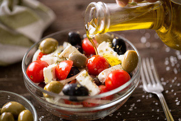 vegetarian salad with fresh vegetables, feta and green olives pouring virgin olive oil.