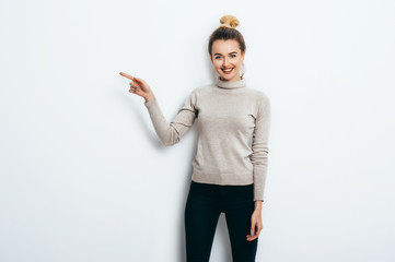 Young beautiful cheerful woman with hair bun wearing in jeans and sweater pointing with forefinger on copy space over white wall. Good mood. People Emotions Beauty Fashion Lifestyle concepts