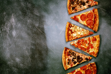 Slices of pizza with different toppings on a dark textured background