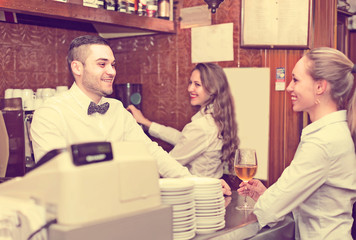female chatting with bartenders