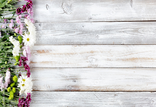 Mixed flowers forming left border on white weathered wooden boards