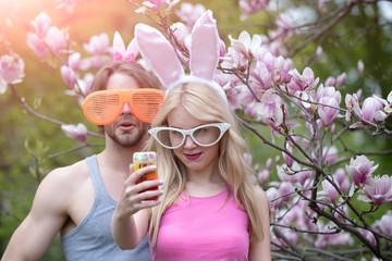 Happy couple in love making selfie at blossoming magnolia trees.