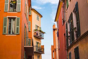 Building facades with balconies and flower pots on a narrow path in Villefranche-sur-mer with blue sky on the background, France