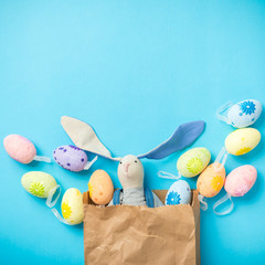 Easter bunny in a paper bag. Rabbit. Blue background. Easter ideas. Easter eggs. Space for text. Easter 2018.