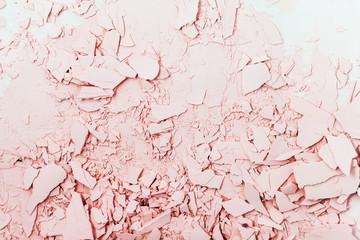 Textured plaster in pink tones. Cracked and broken plaster
